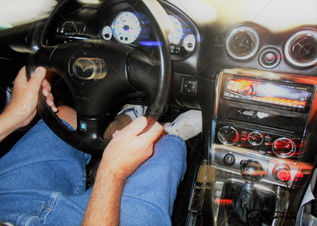 A person driving a stick shift (manual transmission) automobile.